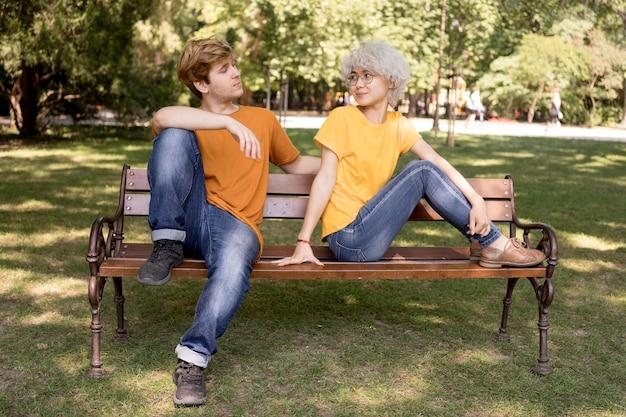 Nettes paar, das im park auf bank entspannt