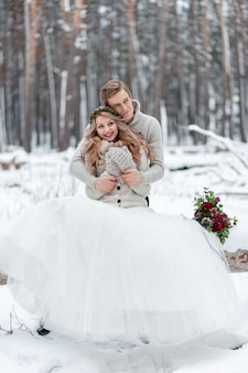 Nettes paar, das in einen blumenstrauß verliebt ist, sitzt auf dem baumstammhintergrund des winterwaldes. kunstwerk. winterhochzeit. speicherplatz kopieren