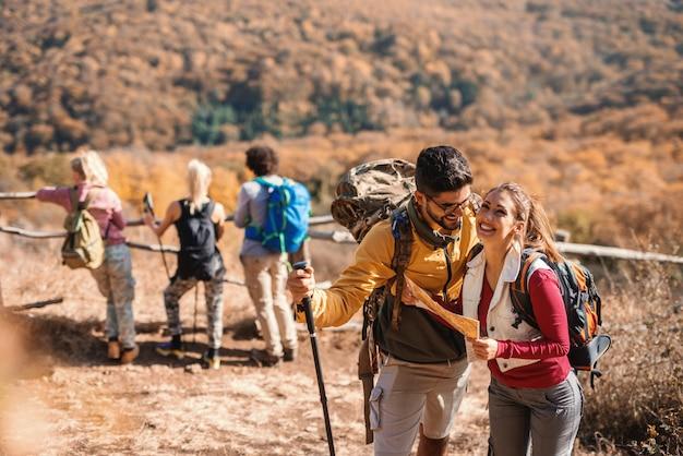 Nettes paar, das karte betrachtet, während ihre freunde im hintergrund ansicht betrachten. wanderkonzept.