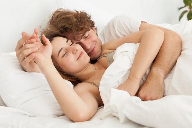 Nettes paar, das mittleren schuss zusammen schläft