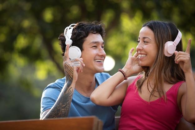 Nettes paar, das musik über kopfhörer hört
