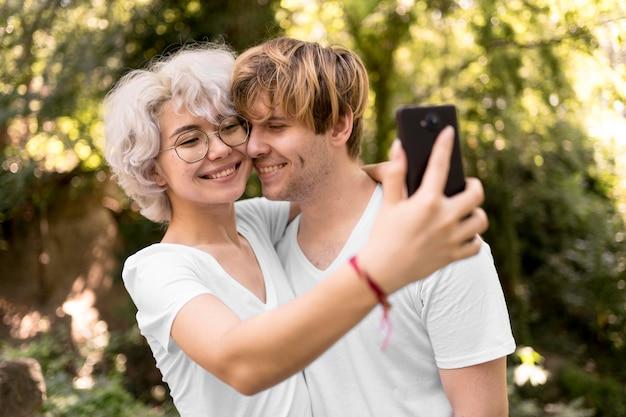 Nettes paar, das selfie zusammen im park nimmt