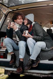 Nettes paar, das tassen kaffee in einem van hält