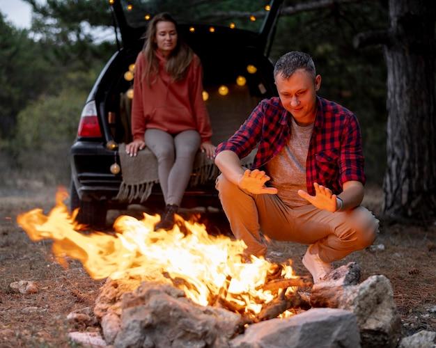 Nettes paar, das zusammen lagerfeuer genießt