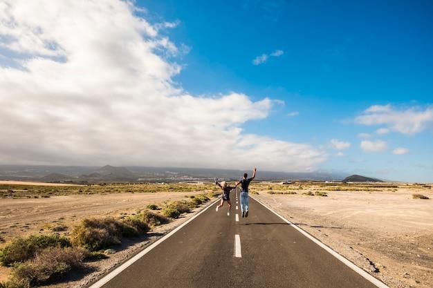 Nettes paar geht und springt mit befriedigung und freude auf einem langen unendlichen weg für das zusammenleben konzept schönen himmel und wüste um mann und frau menschen im glück auf der suche nach dem richtigen weg