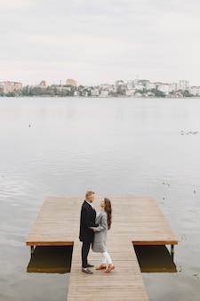 Nettes paar in einem park. dame in einem grauen mantel. leute am pier.