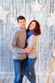 Nettes paar in grauen identischen pullovern umarmt und lächelt für eine kamera
