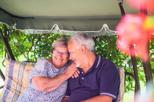 Nettes paar schöne kaukasische senior 70 jahre sitzen draußen zu hause und haben spaß mit lächeln und lachen