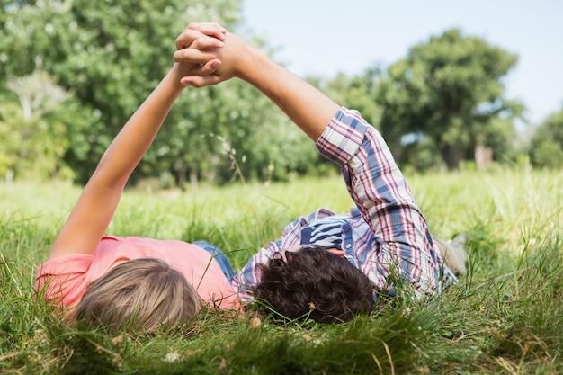 Nettes paarhändchenhalten im park an einem sonnigen tag
