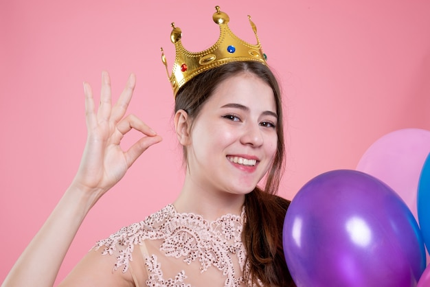 Nettes partygirl der nahaufnahme-vorderansicht mit der krone, die ballons hält, die okey zeichen machen