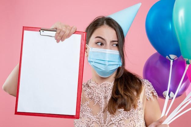 Nettes partygirl der nahaufnahme-vorderansicht mit krone und maske, die luftballons und zwischenablage halten