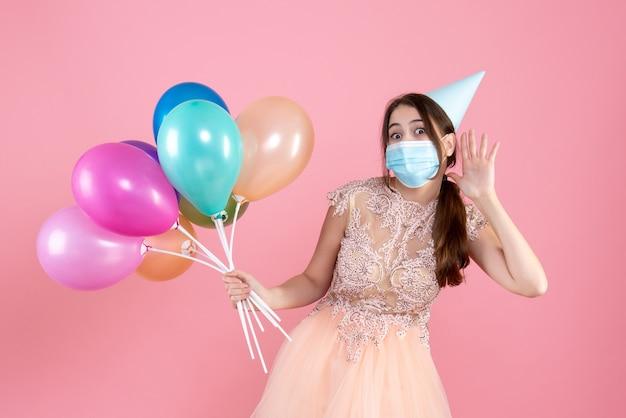 Nettes partygirl der vorderansicht mit der partykappe, die bunte luftballons hält, die etwas hören