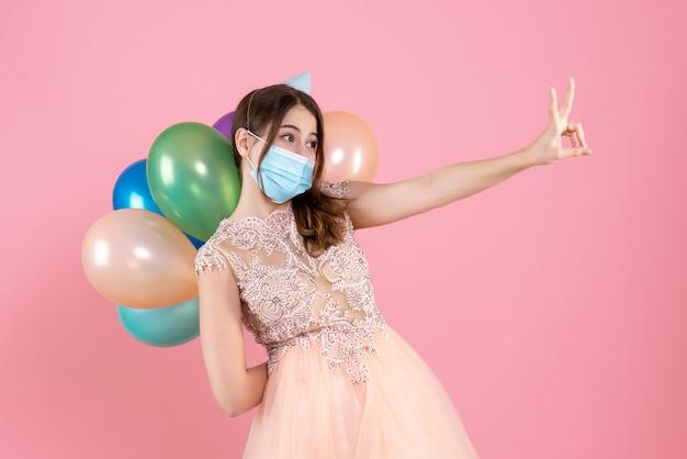 Nettes partygirl der vorderansicht mit der partykappe, die bunte luftballons hinter ihrem rücken hält, der siegeszeichen macht