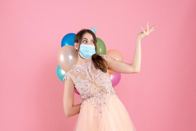 Nettes partygirl der vorderansicht mit der partykappe, die bunte luftballons hinter ihrem rücken hält