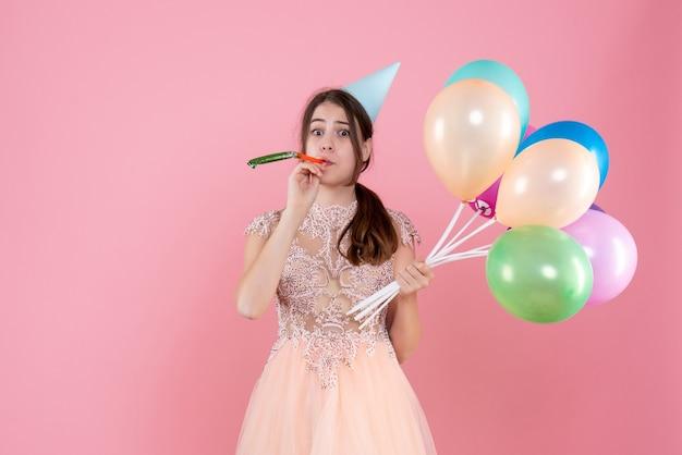 Nettes partygirl der vorderansicht mit partykappe, die luftballons mit krachmacher hält