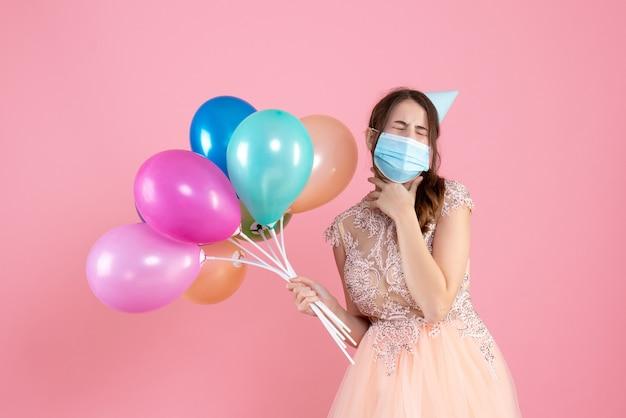 Nettes partygirl der vorderansicht mit partykappe und medizinischer maske, die ihre augen schließt, die bunte luftballons halten