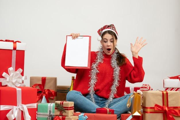Nettes partygirl der vorderansicht mit weihnachtsmütze, die dokumente hält, die um geschenke sitzen