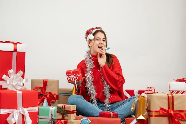 Nettes partygirl der vorderansicht mit weihnachtsmütze, die geschenk unter verwendung des krachmachers hält, der um geschenke sitzt