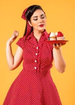 Nettes pinup-mädchen, das mit cupcakes aufwirft