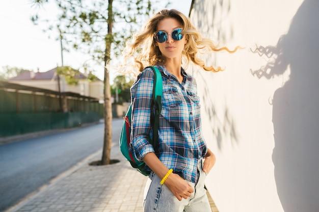Nettes porträt der stilvollen lächelnden glücklichen blonden frau, die in straße mit rucksack geht