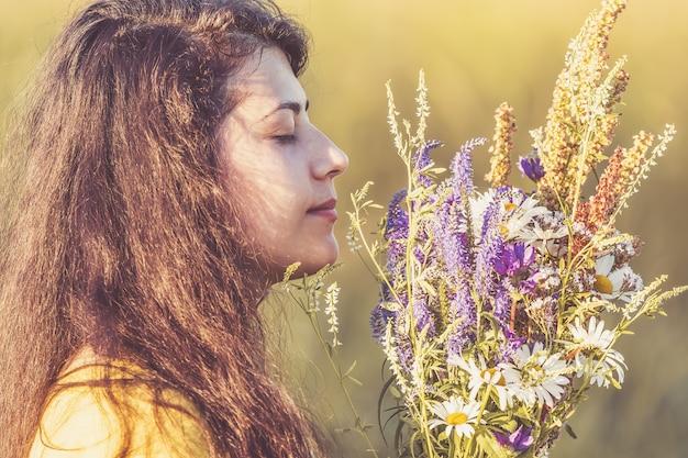 Nettes porträt des jungen mädchens mit feldblumen während des sommersonnenuntergangs