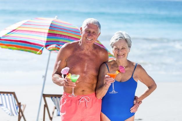 Nettes reifes paar, das cocktails am strand hat