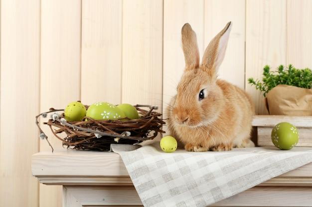 Nettes rotes kaninchen mit ostereiern auf regal auf holzwand
