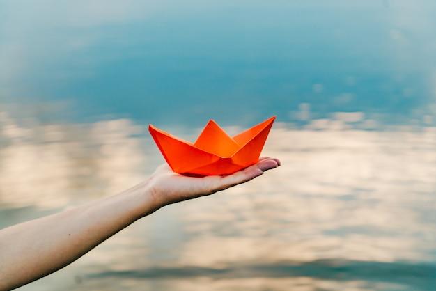 Nettes rotes papierboot auf der hand einer jungen frau über dem wasser im fluss