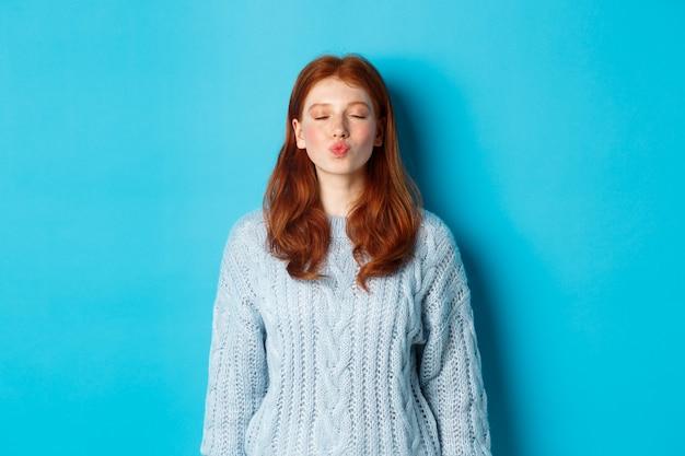 Nettes rothaariges jugendlich mädchen, das auf kuss, fältchenlippen und geschlossene augen wartet, im pullover gegen blauen hintergrund stehend.