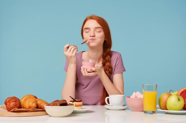 Nettes rothaariges mädchen, das versucht, kirschjoghurt mit einem teelöffel zu probieren, schloss die augen vor vergnügen,