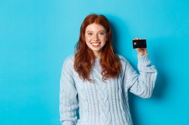 Nettes rothaariges mädchen im pullover, der kreditkarte zeigt, in die kamera lächelt und auf blauem hintergrund steht