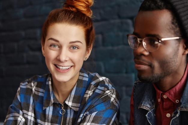 Nettes rothaariges mädchen mit haarknoten, das kamera mit freudigem lächeln betrachtet, das im modernen kaffeehaus entspannt