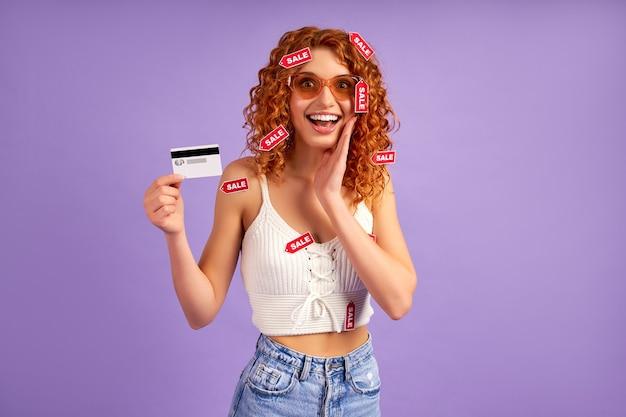 Nettes rothaariges mädchen mit locken und verkaufsetiketten, die kreditkarte einzeln auf lila zeigen