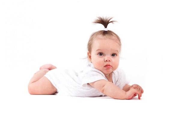 Nettes schönes baby im weißen hemd liegt auf bauch mit milchflasche