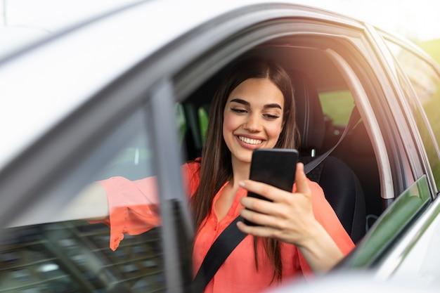Nettes schönes junges frauenlächeln und handy, das den bildschirm im auto während der reise berührt.
