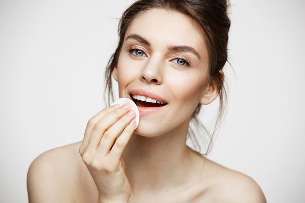 Nettes schönes natürliches brünettes mädchen, das gesicht mit lächelndem baumwollschwamm lächelnd betrachtet kamera über weißem hintergrund. kosmetologie und spa.