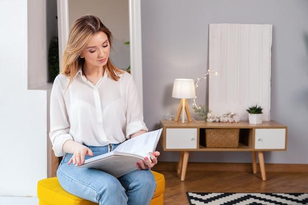 Nettes schönes recht attraktives kaukasisches mädchenmodell im weißen hemd, in den blue jeans, die auf stuhl sitzen und in der zeitschrift lesen.