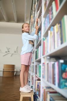 Nettes schulkind posiert für die kamera in der bibliothek