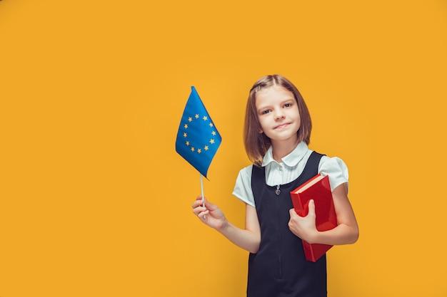 Nettes schulmädchen, das flagge der europäischen union und buch in ihren händen hält bildung in europa-konzept