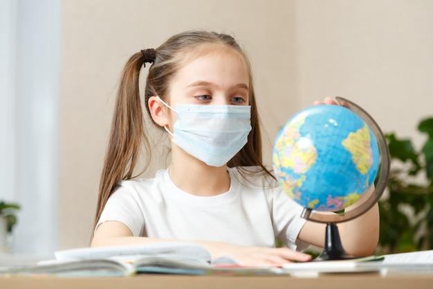 Nettes schulmädchen, das globus zu hause während der quarantäne betrachtet. coronavirus weltweites konzept.