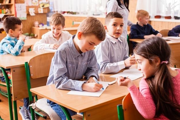 Nettes schulmädchen, das ihrem mitschüler während des unterrichts hilft