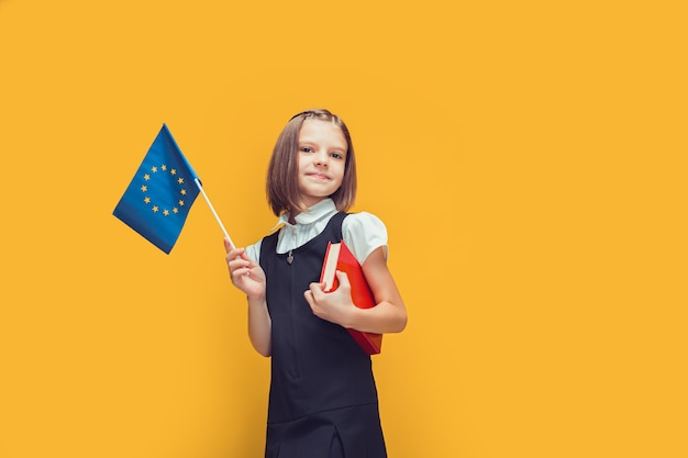 Nettes schulmädchen, das kleine flagge der europäischen union und buch in der hand hält bildung in europa-konzept