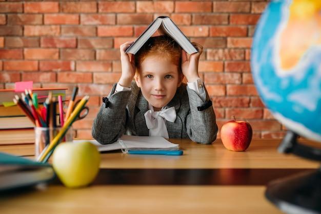 Nettes schulmädchen mit lehrbuch auf ihrem kopf, der am tisch sitzt.