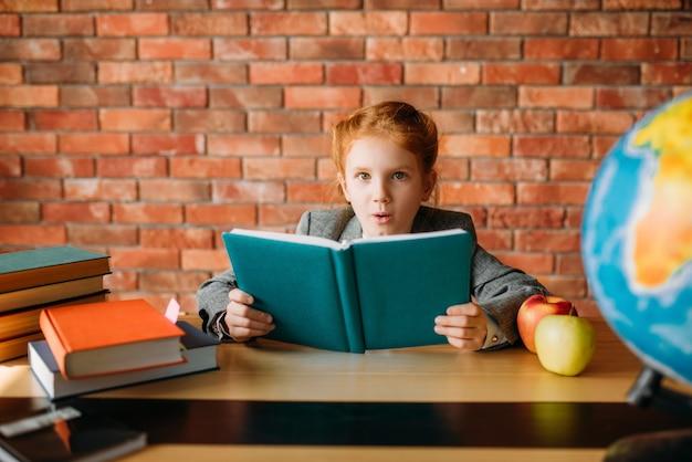 Nettes schulmädchen mit lehrbüchern wirft am tisch auf