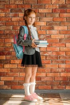 Nettes schulmädchen mit schultasche hält lehrbücher