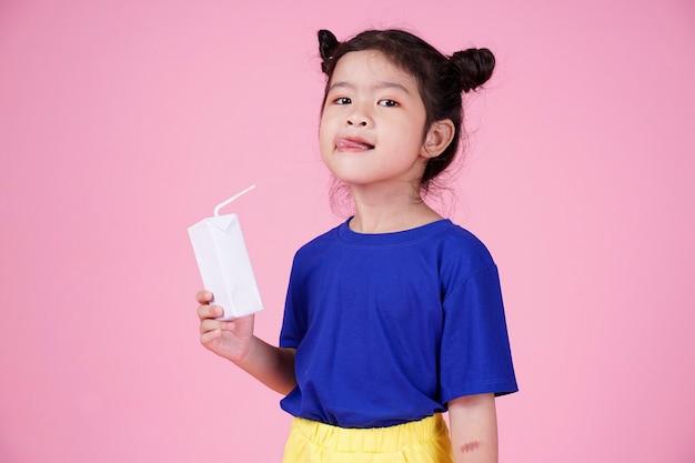 Nettes selbstbewusstes asiatisches kleines kindermädchen trinken milchkiste