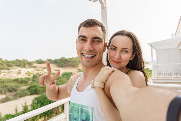 Nettes selfie eines jungen paares, das an der kamera, ein symbol des friedens umarmt und lächelt
