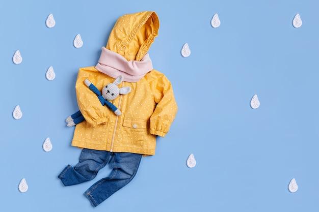 Nettes set von herbst-kinder-outfit. gelber regenmantel mit spielzeughäschen und jeans auf blauem hintergrund. herbststimmung