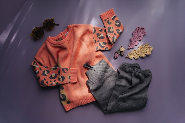 Nettes set von herbst-kinder-outfit. pullover mit leopardenmuster und baumwollhose. herbststimmung