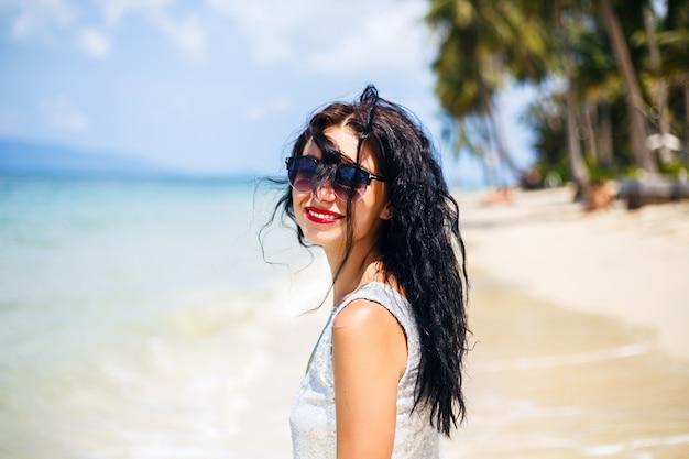Nettes sommermodeporträt der schönheitsbrünettenfrau, die spaß am strand, tanzend und lächelnd hat